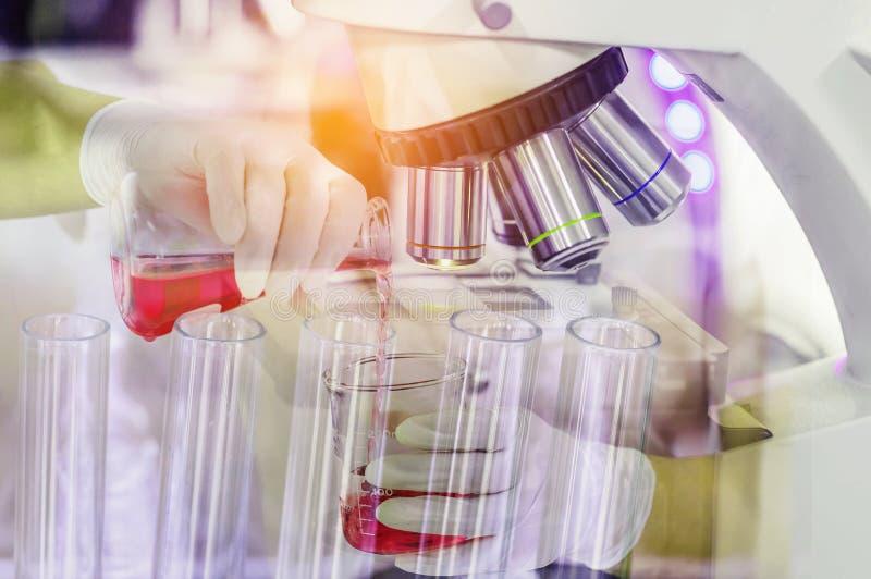 Feche acima do equipamento do microscópio para experiências da pesquisa com líquido levando da química da pesquisa da mulher do c foto de stock