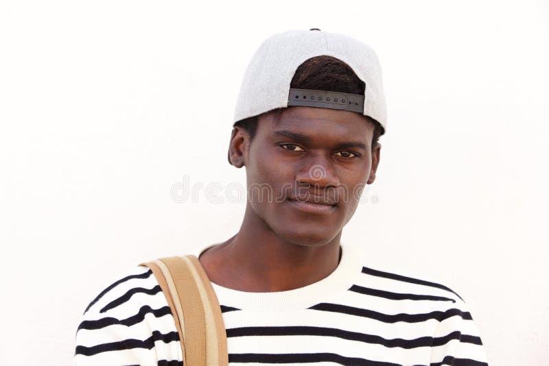 Feche acima do estudante masculino africano novo fresco no tampão contra o fundo branco fotos de stock