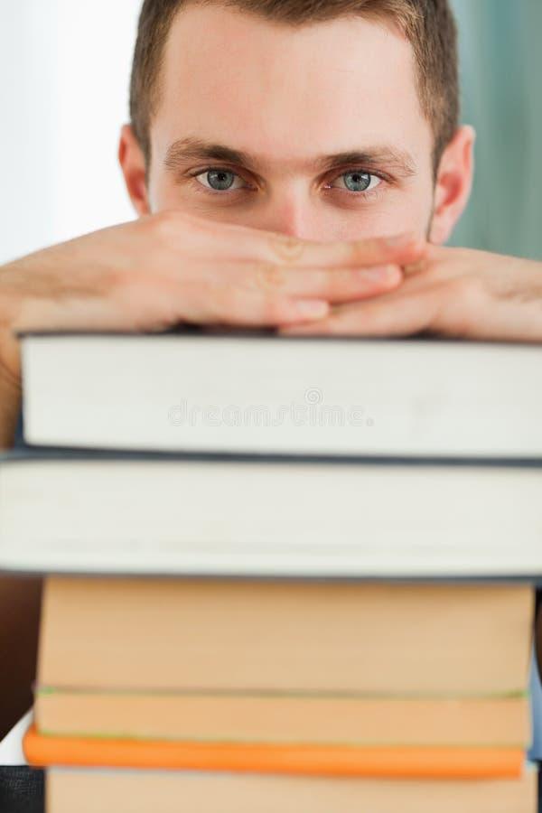 Feche acima do estudante que esconde atrás de uma pilha dos livros fotos de stock royalty free