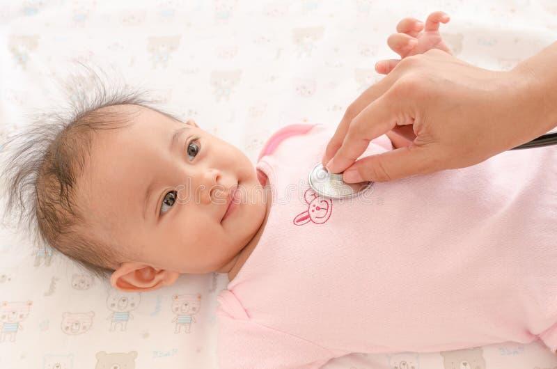 Feche acima do exame médico completo asiático do bebê com estetoscópio fotografia de stock royalty free