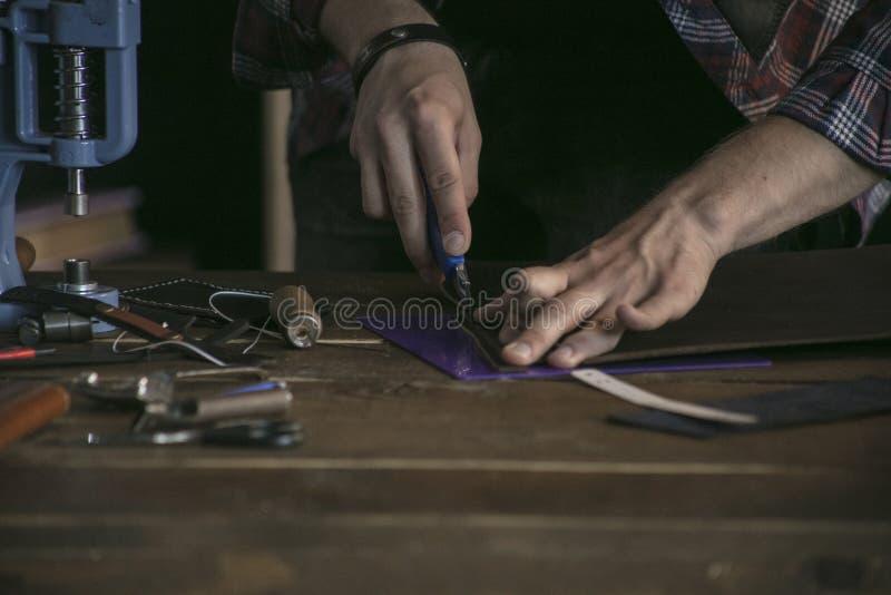 Feche acima do fabricante do couro da mão do homem que trabalha na tabela de madeira com ferramentas imagem de stock royalty free