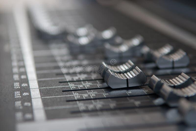 Feche acima do fader de mistura do console do estúdio profissional no cinza imagem de stock royalty free