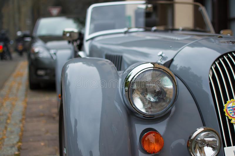 Feche acima do farol de um carro desportivo clássico cinzento, com fundo borrado imagem de stock