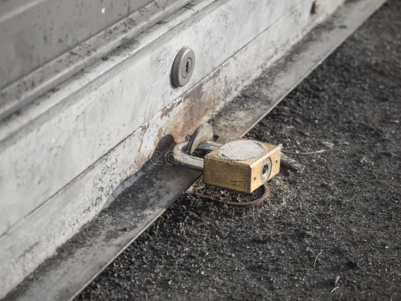 Feche acima do fechamento chave na porta do obturador com o foco seletivo da cor, monocromático fotografia de stock royalty free