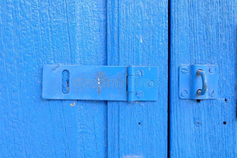 Feche acima do fechamento do ferrolho na porta de madeira azul imagens de stock