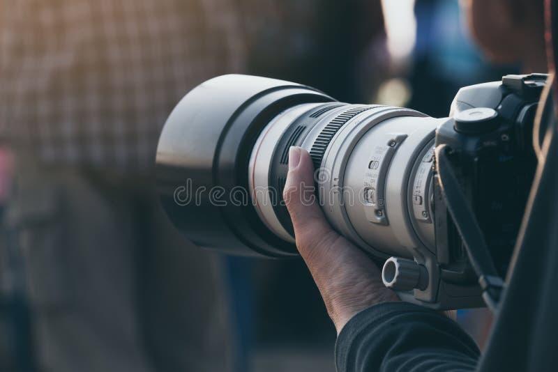Feche acima do fotógrafo que guarda a lente teleobjetiva imagem de stock royalty free