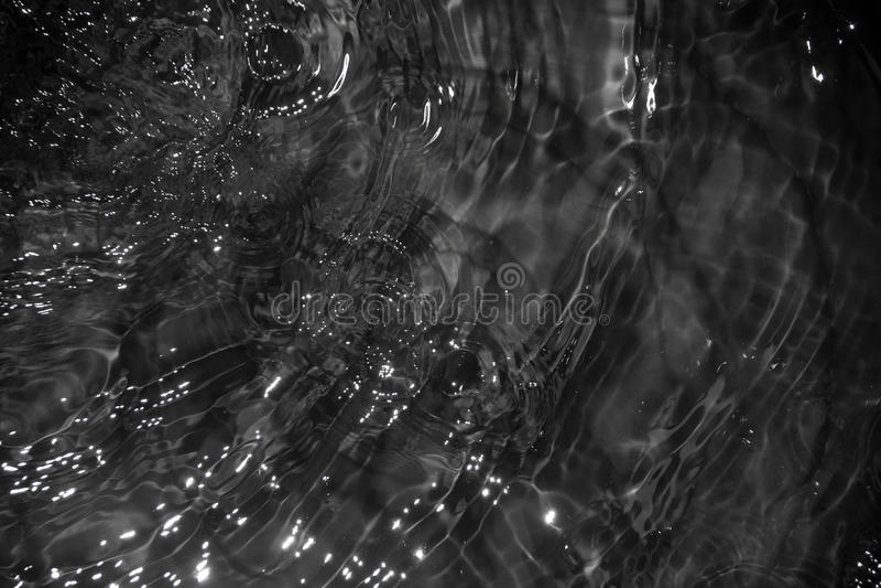 Feche acima do fundo abstrato escuro da onda do movimento da água foto de stock