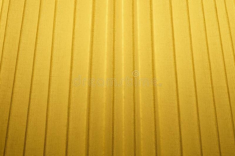 Feche acima do fundo da textura plissada amarelo de matéria têxtil imagem de stock royalty free