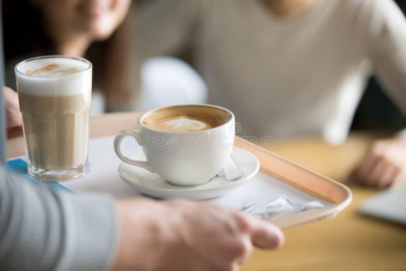 Feche acima do garçom que traz o café quente aos visitantes do café imagem de stock