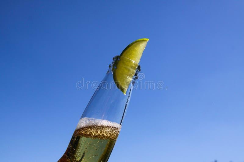 Feche acima do gargalo isolado com cerveja amarela efervescente e de uma fatia de cal contra o céu azul profundo sem nuvens fotos de stock royalty free