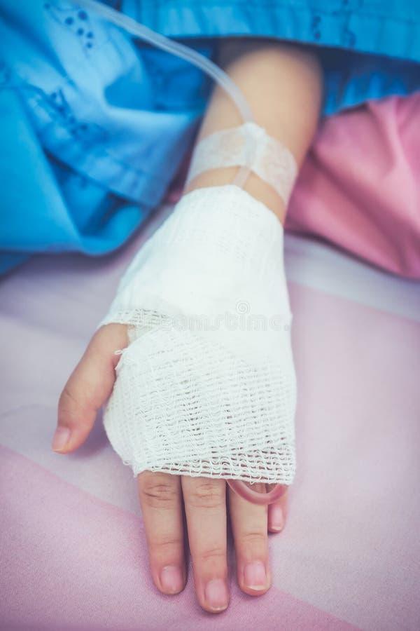 Feche acima do gotejamento salino do iv do intravenous em um paciente ha do ` s da criança fotos de stock