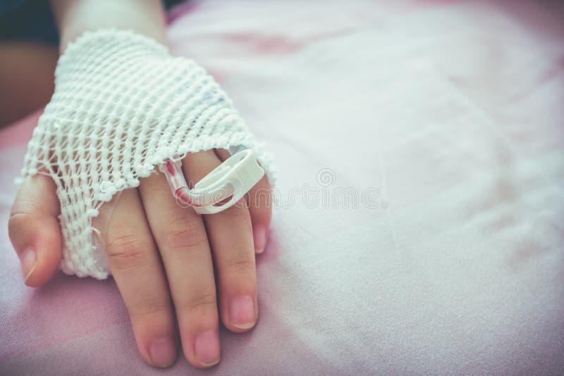 Feche acima do gotejamento salino do iv do intravenous em um paciente ha do ` s da criança foto de stock royalty free
