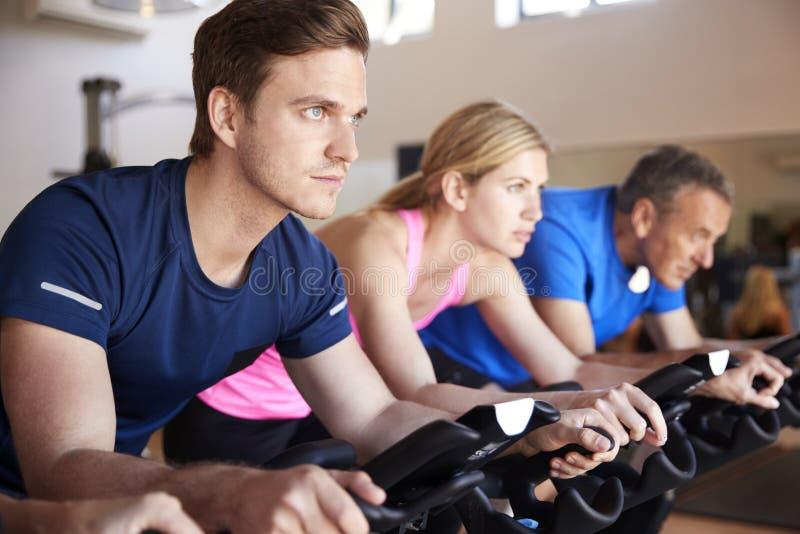 Feche acima do grupo que toma a classe da rotação no Gym foto de stock