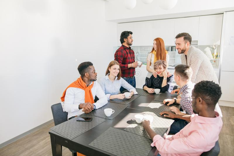 Feche acima do grupo unido da vista lateral de jovens que passam o tempo na cozinha foto de stock