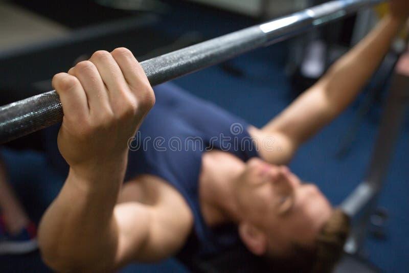 Feche acima do homem com barbell que exercita no gym foto de stock royalty free