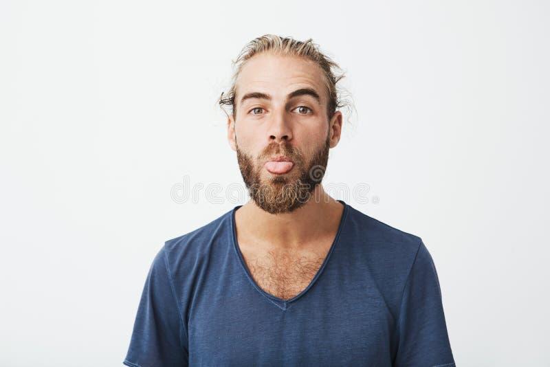 Feche acima do homem considerável engraçado com bom penteado e da barba no t-shirt azul que faz a cara parva in camera Linguagem  foto de stock
