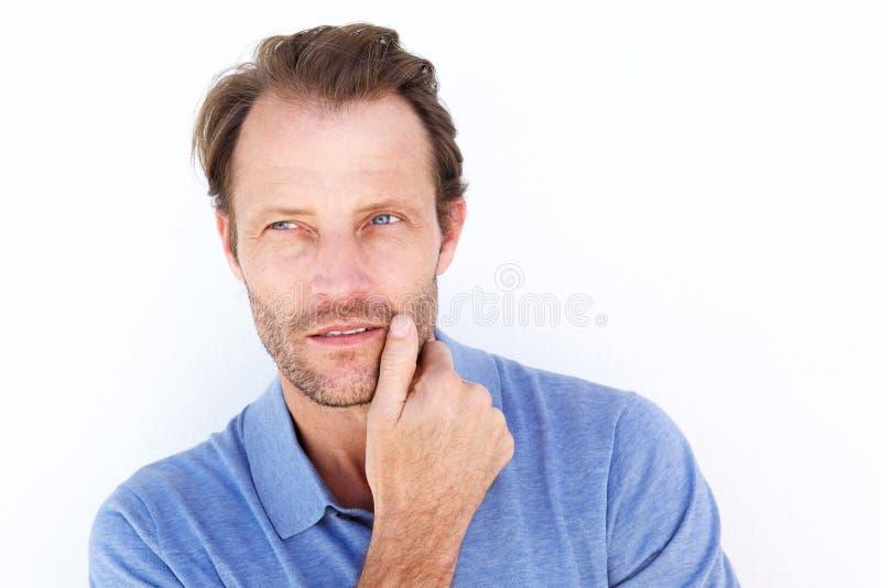 Feche acima do homem considerável que pensa com mão no queixo foto de stock royalty free