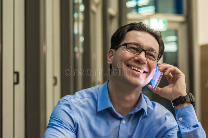 Feche acima do homem de negócios de sorriso usando o telefone esperto moderno, foto de stock royalty free