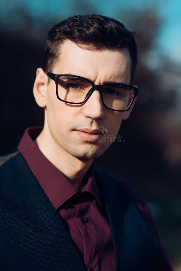 Feche acima do homem de negócios novo Wearing Eyeglasses, olhando a câmera contra o fundo natural fotografia de stock