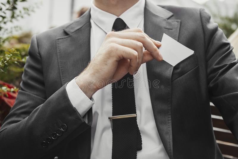 Feche acima do homem de negócios que põe o cartão vazio em seu bolso do revestimento fotos de stock
