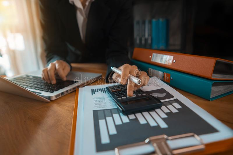 Feche acima do homem de negócios que trabalha na calculadora para calcular financeiro fotografia de stock