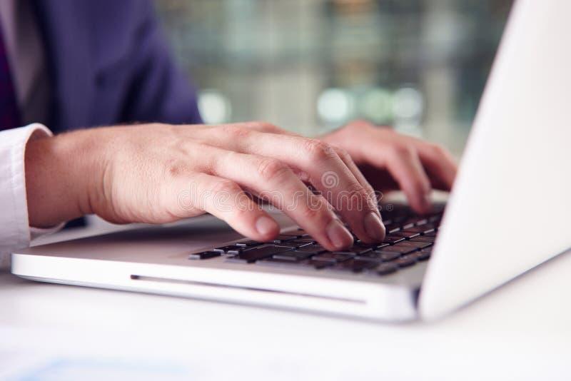 Feche acima do homem de negócios? s entrega usando o teclado de um portátil imagens de stock royalty free