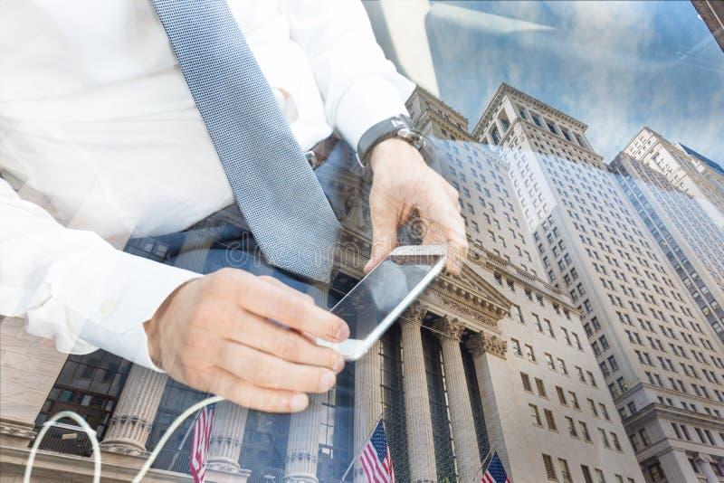 Feche acima do homem de negócios usando o telefone esperto móvel no táxi contra a reflexão da Bolsa de Nova Iorque foto de stock