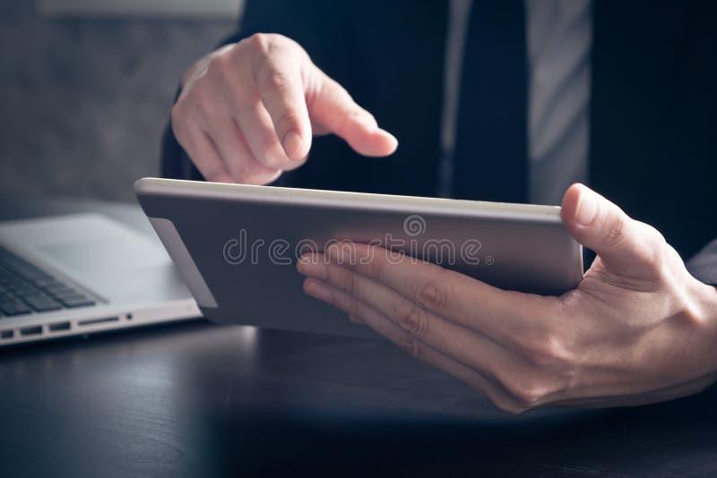 Feche acima do homem de negócios usando a tabuleta na mesa de escritório imagens de stock royalty free