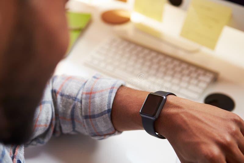 Feche acima do homem de negócios Wearing Smart Watch no escritório de projeto fotografia de stock royalty free