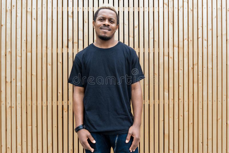 Feche acima do homem de pele escura atrativo no t-shirt preto no fundo de madeira fotos de stock royalty free