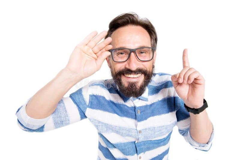 Feche acima do homem de sorriso que aponta seu dedo acima ao estar feliz imagem de stock