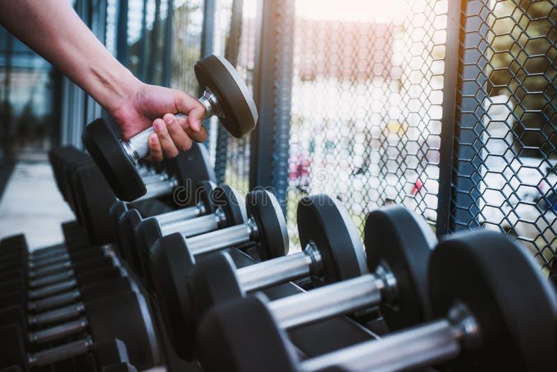 Feche acima do homem do exercício da mão com peso para dobrar os músculos no gym Conceito saudável do estilo de vida fotos de stock royalty free