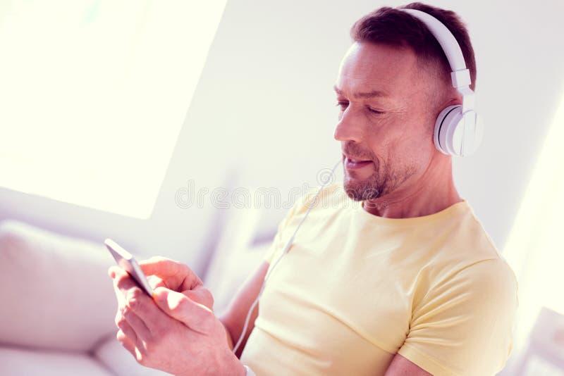 Feche acima do homem maduro farpado que sente curioso ao verificar o e-mail no telefone fotos de stock royalty free