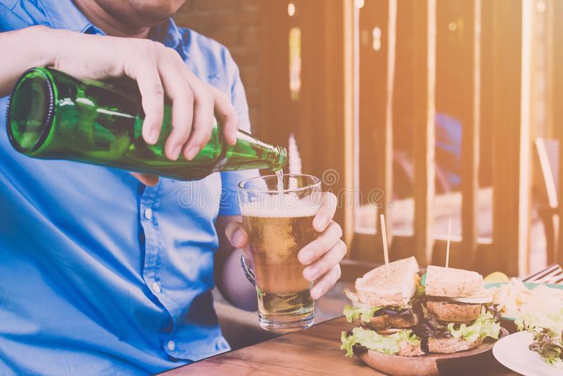Feche acima do homem na cerveja de derramamento da camisa azul, comemore os feriados sexta-feira imagem de stock