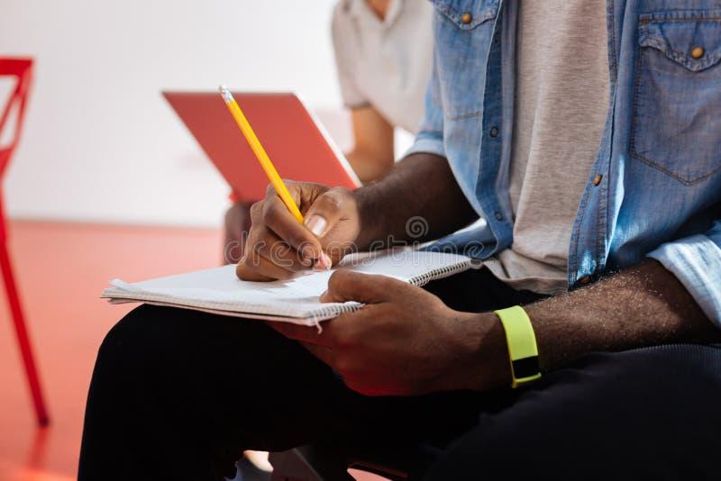 Feche acima do homem negro que faz anotações em seu caderno fotografia de stock