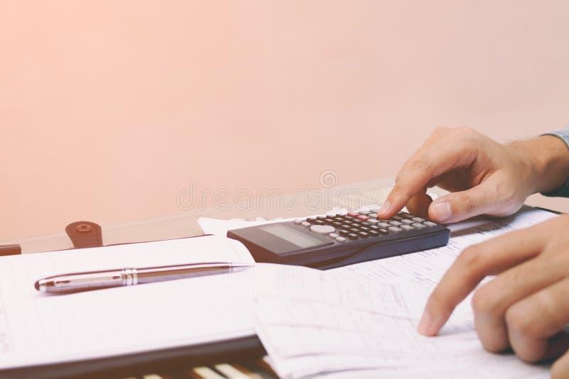 Feche acima do homem novo com a calculadora que conta em casa com espaço da cópia, imagem de stock royalty free
