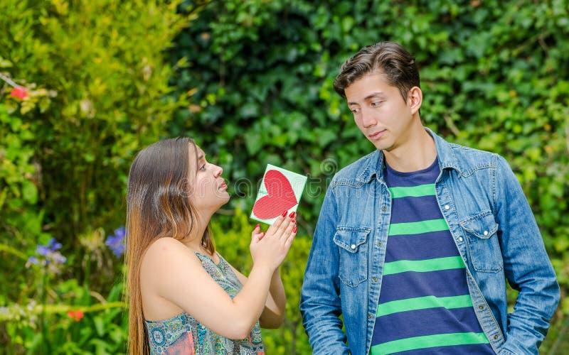 Feche acima do homem novo com uma cara repugnante que olha a menina e a mulher bonita que imploram a seu esmagamento com uma letr fotografia de stock