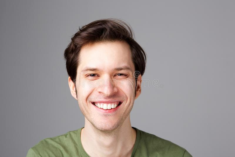 Feche acima do homem novo feliz que está pela parede cinzenta fotos de stock