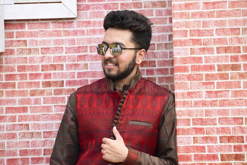 Feche acima do homem novo no vestuário indiano contra uma parede de tijolo, Pune da cerimônia de casamento foto de stock royalty free