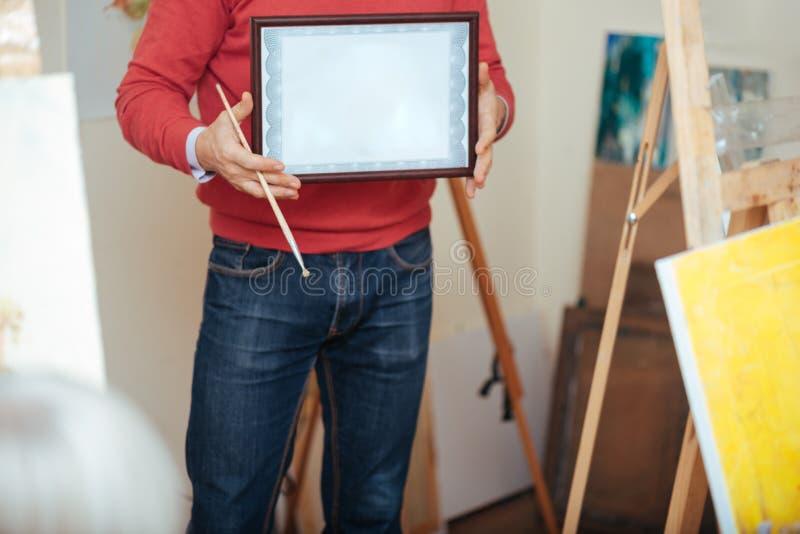 Feche acima do homem novo que demonstra um diploma dos pintores foto de stock royalty free