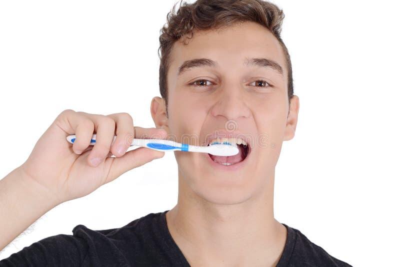 Feche acima do homem novo que escova seus dentes imagens de stock