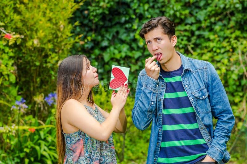 Feche acima do homem novo que faz uma cara repugnante com um dedo em sua boca quando a menina bonita implorar à sua foto de stock royalty free