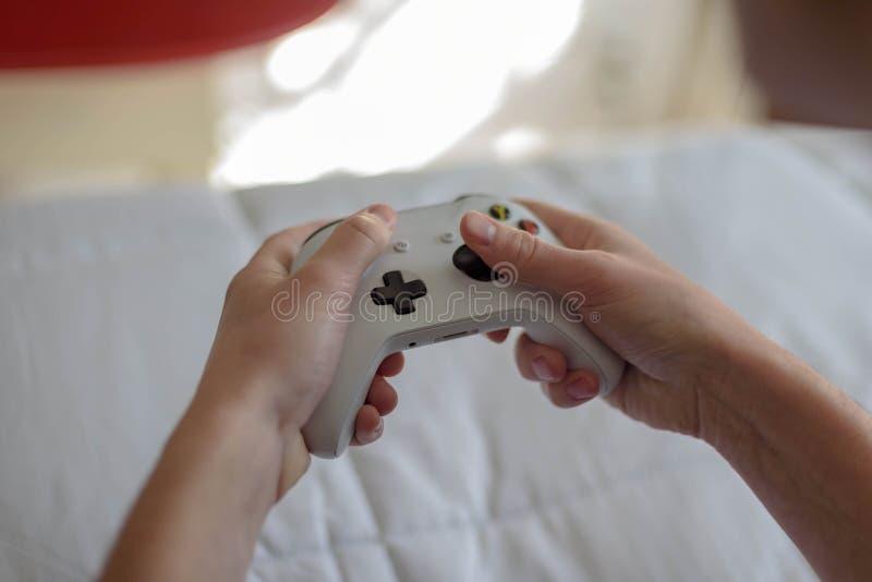 Feche acima do homem novo que guarda o controlador do jogo de vídeo quando playin foto de stock