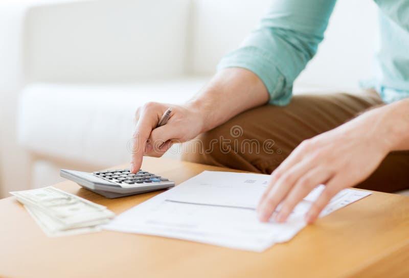 Feche acima do homem que conta o dinheiro e que faz anotações imagens de stock royalty free