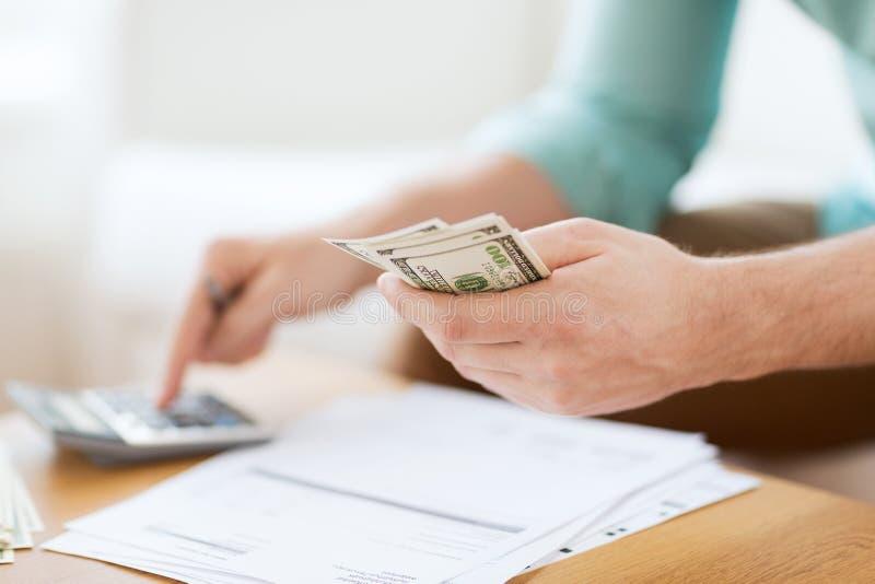 Feche acima do homem que conta o dinheiro e que faz anotações imagem de stock