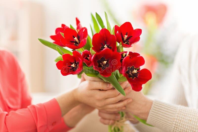 Feche acima do homem que dá flores vermelhas da tulipa à mulher imagens de stock royalty free