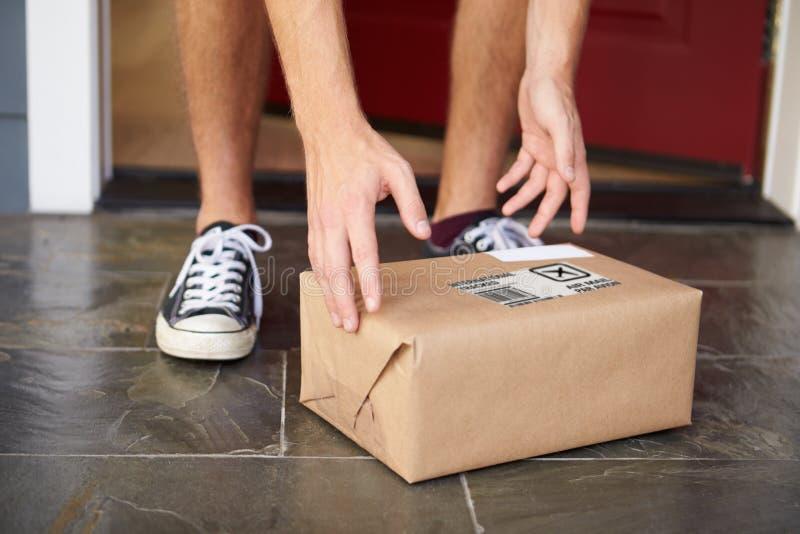 Feche acima do homem que recolhe a entrega do pacote fora da porta fotos de stock