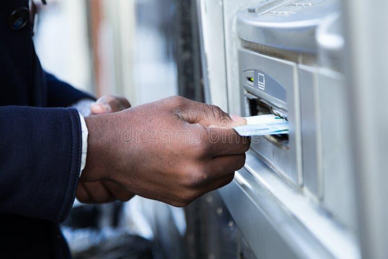 Feche acima do homem que toma o dinheiro do ATM com cartão de crédito fotos de stock