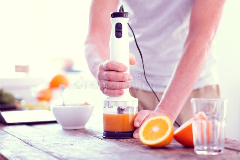 Feche acima do homem que usa o misturador da mão que espreme a laranja fresca para o café da manhã adiantado foto de stock royalty free