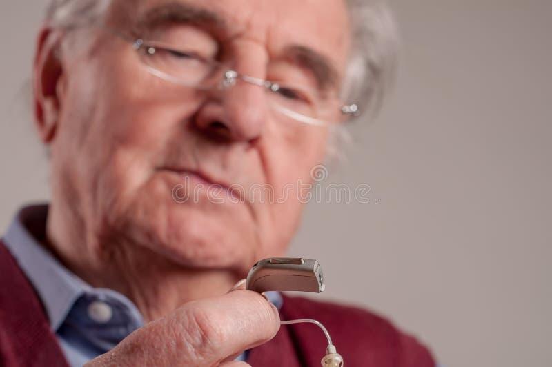 Feche acima do homem superior que guarda a prótese auditiva foto de stock